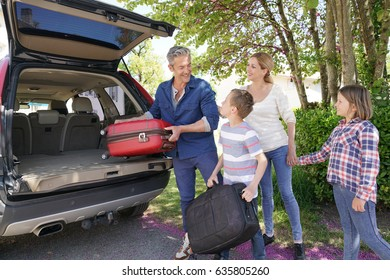 Happy family loading luggage in vehicle