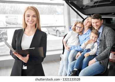 Happy family looking at camera, smiling and sitting in trunk of new automobile. Manager, beautiful woman working in dealership showroom with potential buyers of cars. Blonde holding folder, posing.