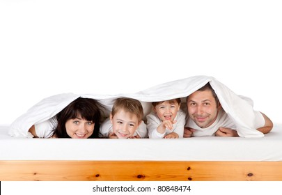 Happy family looking out from blanket or duvet under bed; white studio background.