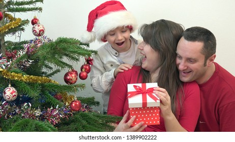 Happy family looking surprised at gift box close Christmas tree