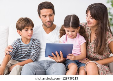 Happy family looking at tablet pc on the couch
