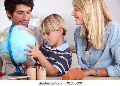 happy family looking terrestrial globe