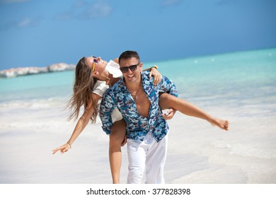 Happy family in love on beach summer vacations. Wife piggybacking on young husband playing and having fun in sunny tropical destination for travel holiday.