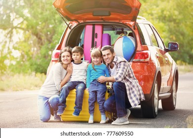 Happy family with luggage near car. Traveling concept