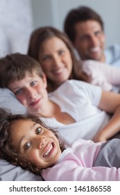 Happy family lying in the bed at home