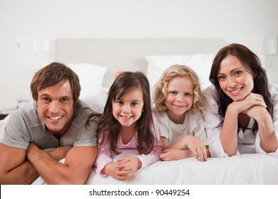 Happy family lying in a bed together