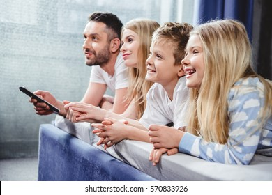 Happy family lying in bed and watching tv with remote controller