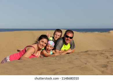 Happy family lying down on Maspalomas sand dunes. Young parents and children portrait at famous landmark in Gran Canaria, Spain. Summer vacation, travel destination concepts