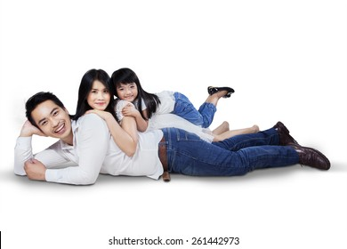 Happy family lying down on the floor while smiling at the camera, isolated over white background