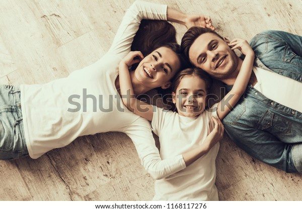 Happy Family Lying of Floor Together at Home. Beautiful Woman Handsome Man and Adorable Little Girl Lying on Parquet Floor and Hugging. Parents and Child Together. Family and Parenthood Concept