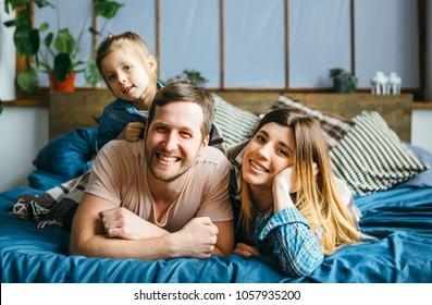 Happy family lying on bad.