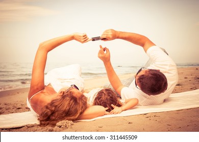 Happy family lying on the beach at the day time. Concept of friendly family.