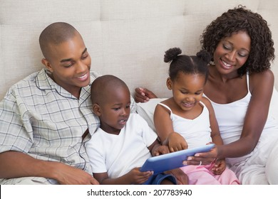Happy family lying on bed using tablet pc at home in the bedroom