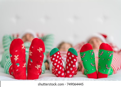 Happy family lying on bed. Mother; father and child having fun in Christmas time. Man, woman and kid relaxing at home. Winter holiday Xmas and New Year concept