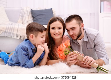 Happy family lying on carpet beside sofa in the room