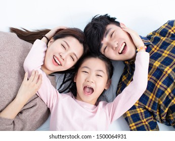 happy family lying on floor looking at camera