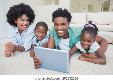 Happy family lying on the floor using tablet at home in the living room