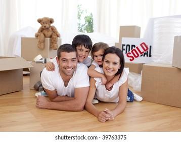 Família feliz deitado no chão depois de comprar casa nova