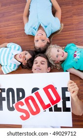 Happy family lying on floor after buying a new house