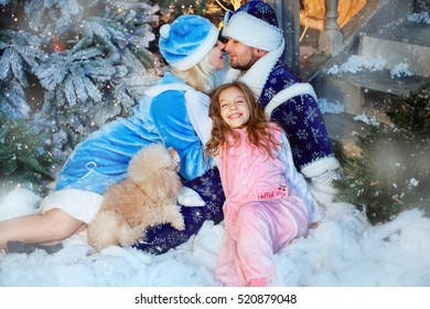 Happy family lying on the snow in winter forest,