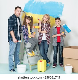 Happy family makes repairs at home. Smiling family painting big Ukrainian flag on wall at home