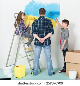 Happy family makes repairs at home. Smiling children painting big Ukrainian flag on wall at home