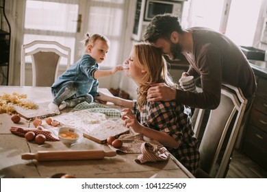 Happy family making pasta in the kitchen at home