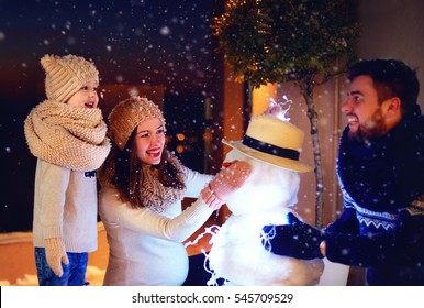 happy family making snowman in evening light under winter snow