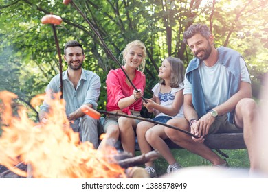 Happy family with male friend roasting sausages over campfire at park