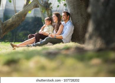 Feliz familia con hombres, mujeres y niños apoyándose en un árbol en el parque de la ciudad. Copiar espacio