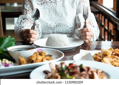 Happy family meal with full food on table asian elder mother hand holding fork, knife, rice on plate & table. Enjoy true authentic exotic homemade healthy Thai meal with child on holidays thanksgiving