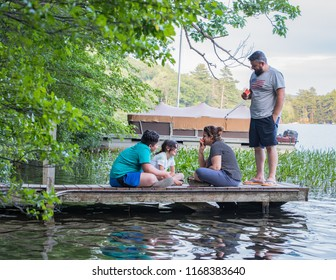 Happy family members eating watermelon on a dock