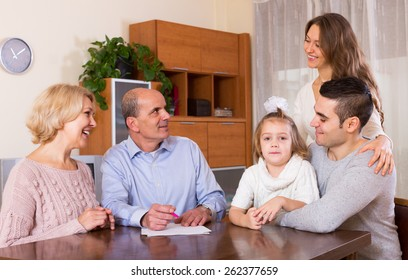 Happy family members ready to sign banking documents at home or office