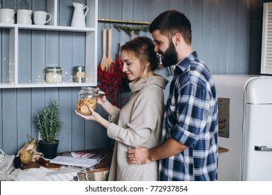 Happy family and Merry Christmas! Young loving happy couple have a good time at christmas morning at cozy home in the kitchen. Love, holidays, christmas, beauty concept