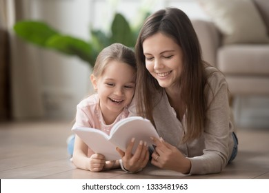 Happy family mom baby sitter and cute kid daughter having fun with book lying on warm floor, smiling mother teaching little girl learning reading story, parent with child educational activity at home
