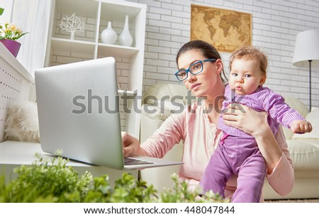 happy family. mom and baby. a young mother working with laptop at home