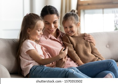 Happy family mom and cute little children daughters using smart phone look at screen, smiling mother with small girls enjoy play game app watch videos with kids learn mobile tech sit on sofa at home