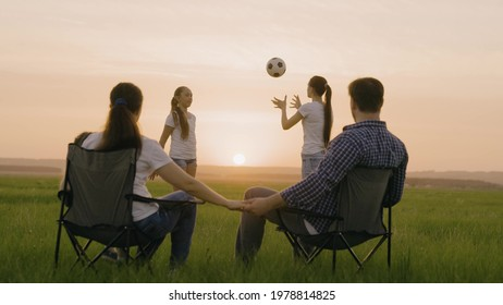 Happy family. Mom and dad are sitting in tourist chairs in field, children are playing ball in sun. Travelers, mom, dad, children on vacation play together at sunset in park. Healthy family, childhood
