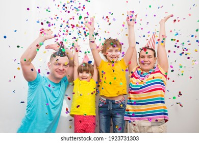 happy family mom, dad and two kids  brother and sister with confetti on colored
