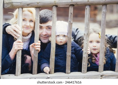 Happy family - mom, dad and two daughters playfully looks through a fence outdoors in Autumn.