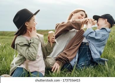 2人の子どもを持つ母親が野原で歩き休む