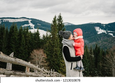 Happy family: mom and girl are having fun and playing on snowy winter, walk in mountain, nature. Mother and children daughter enjoying journey. Frost winter season.
