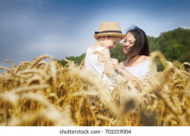 Happy family. Mom and son are laughing and talking on the wheat field. Front view.