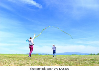 Happy family, mom and son, playing with flying kite on meadow in beautiful spring sunny day, blue sky in background