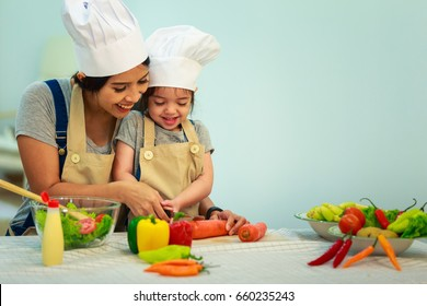 Happy family mom teaching cute girl preparing and cooking healthy salad for the first time. first lesson and healthy lifestyle concept.