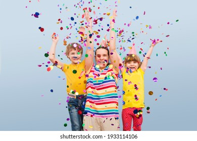 happy family mom and two kids  brother and sister with confetti on colored