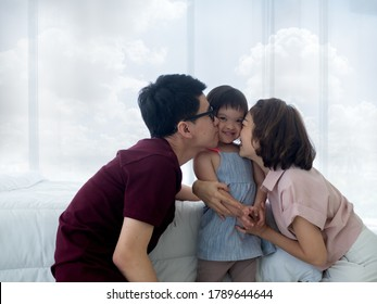 Happy family moments. Asian parents kissing  disable or down syndrome or trisomy 21 young daughter in the bedroom