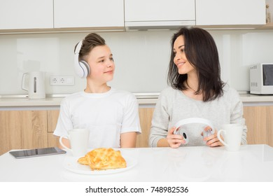 Happy family in the morning. Beautiful woman with her son having breakfast in kitchen, listen music and smiling