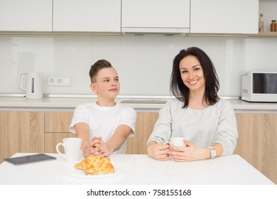 Happy family in the morning. Beautiful woman with her son having breakfast in kitchen. Looking at camera and smiling