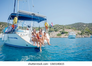 Happy family - mother with adorable daughter and son resting on a yacht